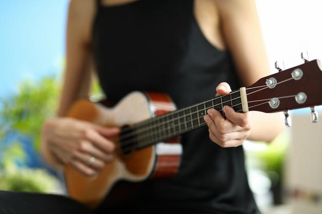 Uma mulher de vestido preto está aprendendo a tocar ukulele. garota afina uma miniatura de guitarra antes de um show