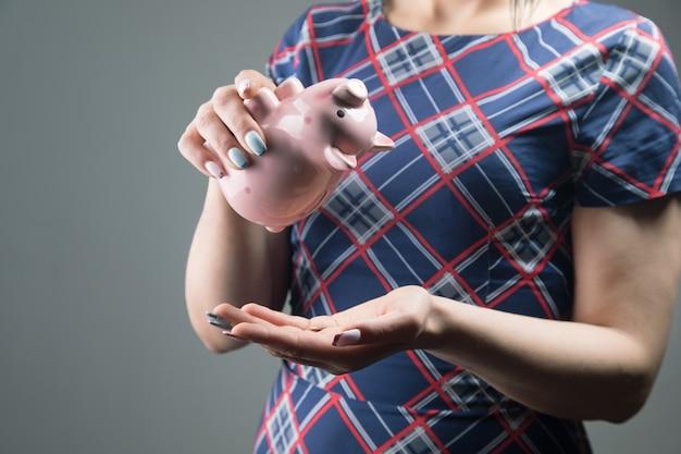 Uma mulher de vestido tira dinheiro de um cofrinho