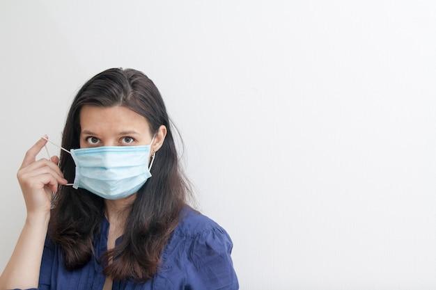 Uma mulher decola ou coloca uma máscara médica. o conceito de coronavírus de quarentena com espaço de cópia