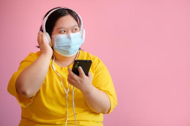 Uma mulher deficiente com síndrome de down aprendendo a ouvir música com um smartphone ela é uma estudante deficiente com síndrome de down usando uma máscara médica