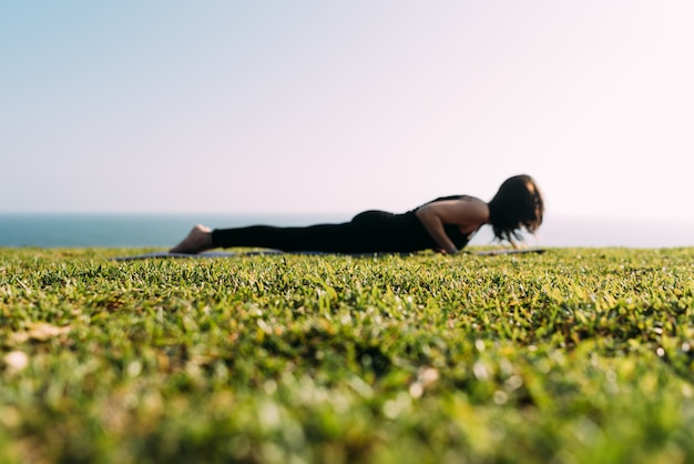 Uma mulher deitada na grama praticando ioga está fora de foco. copie o espaço