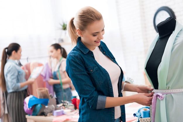 Uma mulher deles está medindo novo vestido.
