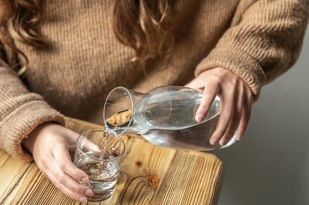 Uma mulher derrama água em um copo de uma garrafa de vidro