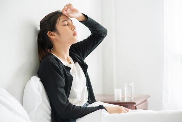 Uma mulher desconfortável se senta na cama e tem um remédio na mesa.