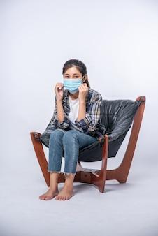 Uma mulher desconfortável sentada em uma cadeira e usando uma máscara