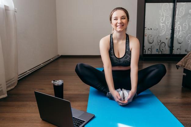 Uma mulher desportiva no sportswear está sentada no chão