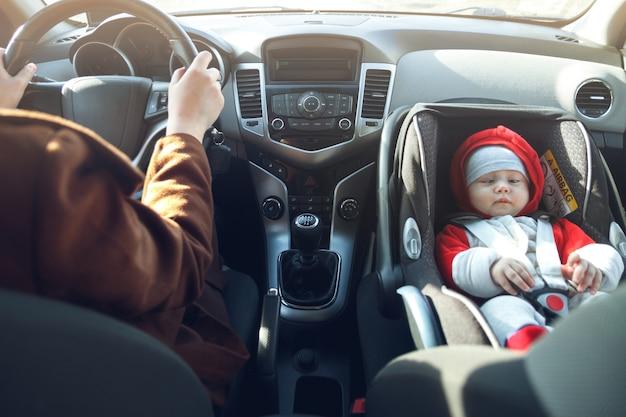 Uma mulher dirige o carro e seu filho pequeno senta-se na cadeirinha do bebê, presa por um cinto de segurança.