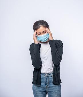 Uma mulher doente com dor de cabeça usava uma máscara e colocou a mão na cabeça.