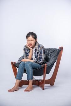 Uma mulher doente com dor de dente e uma mão segurando a bochecha