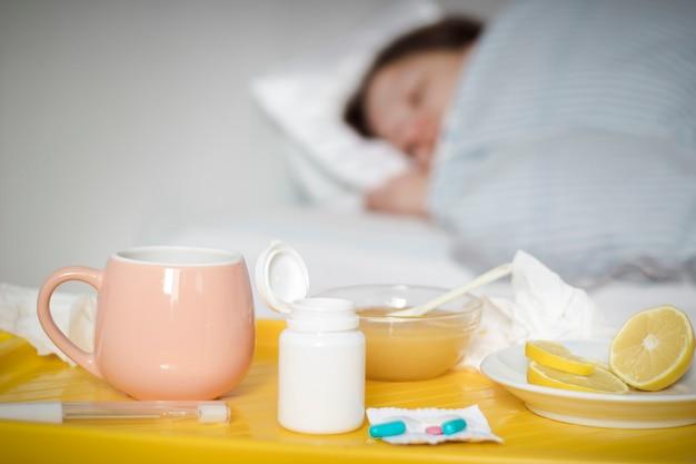 Uma mulher doente com um resfriado ou gripe está deitada na cama com febre.