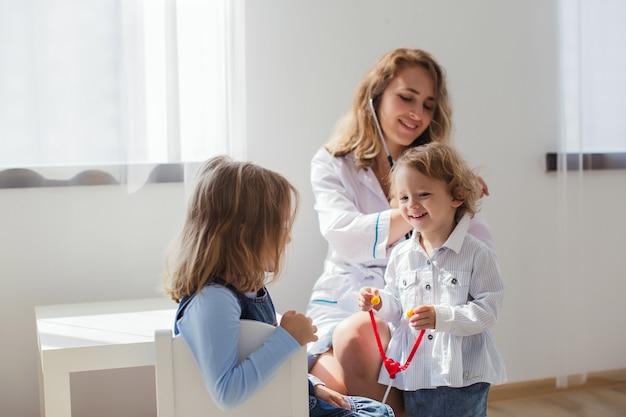 Uma mulher e duas meninas estão brincando de médico em uma aconchegante sala iluminada pela janela