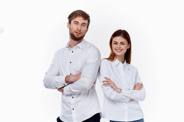 Uma mulher e um homem de camisa branca estão parados um ao lado do outro com os braços cruzados.