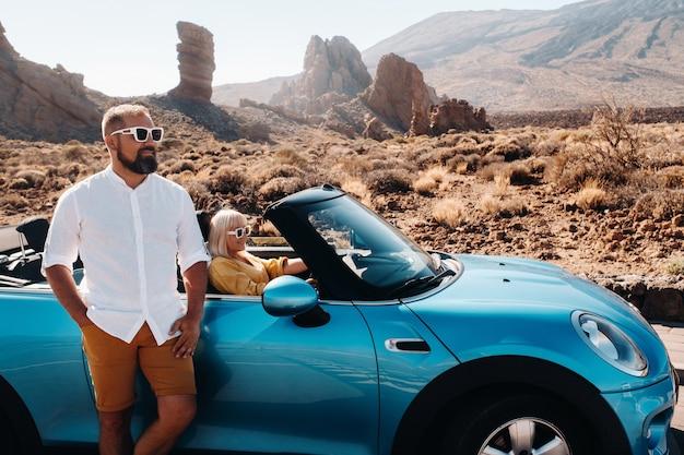 Uma mulher e um homem de óculos em um carro conversível em uma viagem à ilha de tenerife. a cratera do vulcão teide, nas ilhas canárias, na espanha.