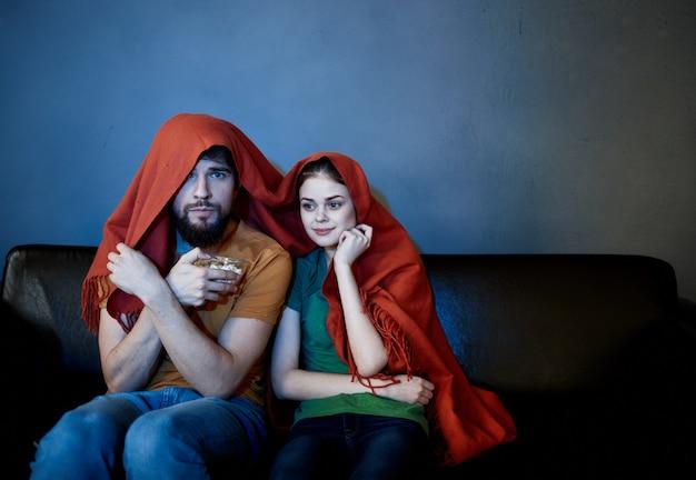 Uma mulher e um homem debaixo de um cobertor vermelho no sofá assistindo tv à noite