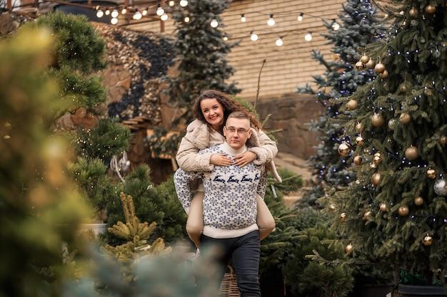 Uma mulher e um homem estão parados perto da árvore de natal, eles estão felizes, clima de ano novo