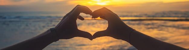 Uma mulher e um homem fazem as mãos um coração ao pôr do sol