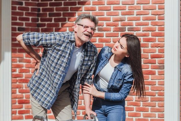 Uma mulher e um homem idoso em uma cadeira de rodas no lar de idosos. a mulher cobriu o pai