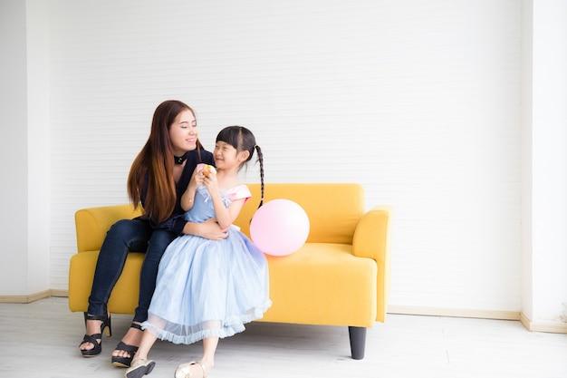 Uma mulher e uma menina estão sorrindo e se abraçando alegremente no sofá.