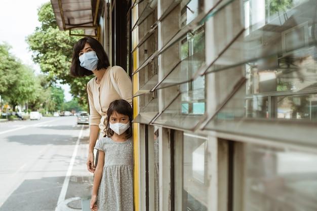 Uma mulher e uma menina usando uma máscara estão esperando o ônibus no ponto de ônibus