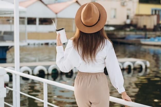 Uma mulher elegante beber café e caminhar à beira-mar em um dia quente de verão no por do sol