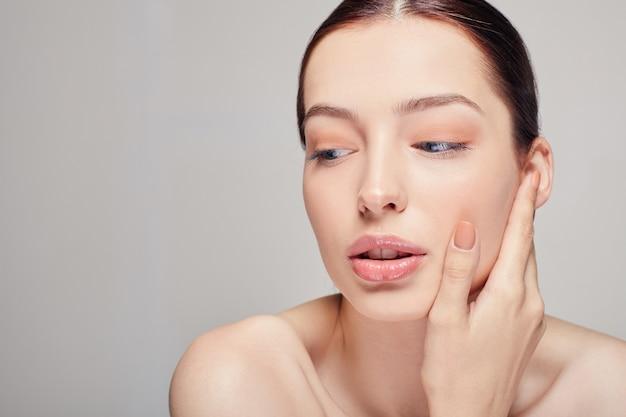 Uma mulher elegante e sofisticada, com lábios carnudos, cabelos escuros e pele delicada limpa e radiante