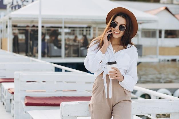 Uma mulher elegante falando por telefone e caminhar ao longo da praia em um dia quente de verão ao pôr do sol