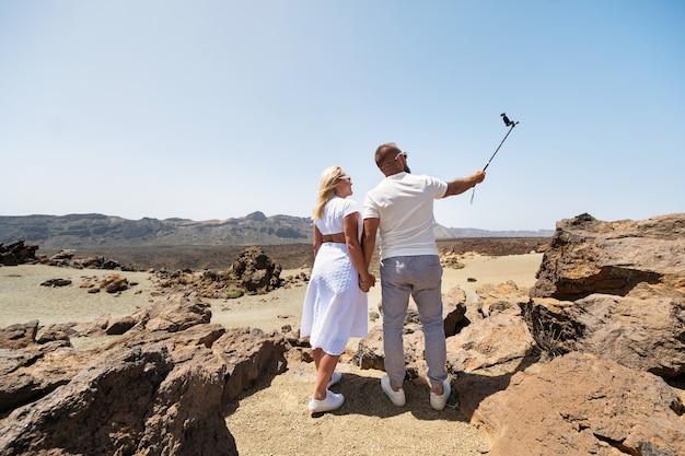 Uma mulher elegante tira uma selfie na cratera do vulcão teide. paisagem do deserto em tenerife.