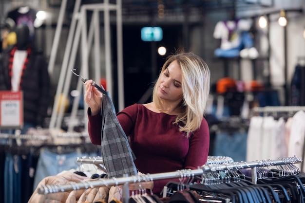 Uma mulher elegante, verificando a nova coleção em uma loja de roupas
