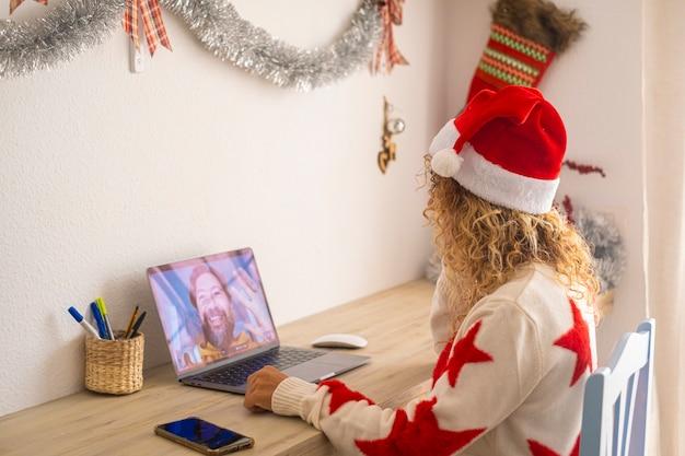 Uma mulher em casa, sentada na área de trabalho, usa o laptop para fazer uma videochamada com o marido para celebrar o natal juntos - pessoas modernas distantes, estilo de vida amoroso - mulher com chapéu de papai noel usam a internet