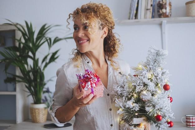 Uma mulher em casa sorri e segura o presente de natal e a árvore olhando para o lado dela. temporada de feriados de dezembro e celebração. mulheres felizes em comemorar e trocar