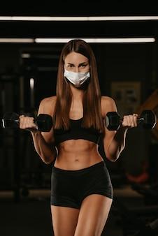 Uma mulher em forma com uma máscara facial para evitar a propagação do coronavírus está fazendo bíceps com halteres. uma garota esportiva com uma máscara cirúrgica está posando durante o treino de braços no ginásio.