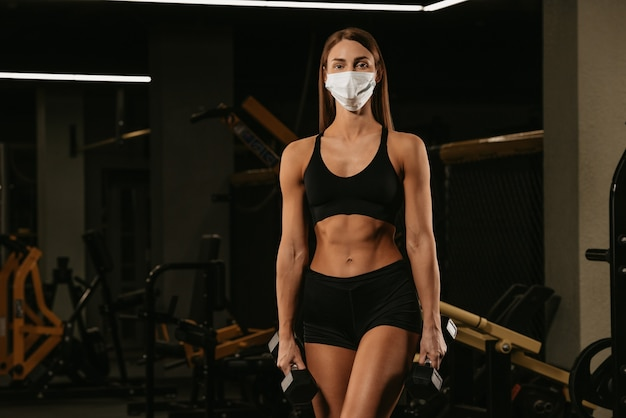 Uma mulher em forma com uma máscara facial para evitar a propagação do coronavírus está posando com halteres. uma garota esportiva com uma máscara cirúrgica está posando após o treino de braços em uma academia.