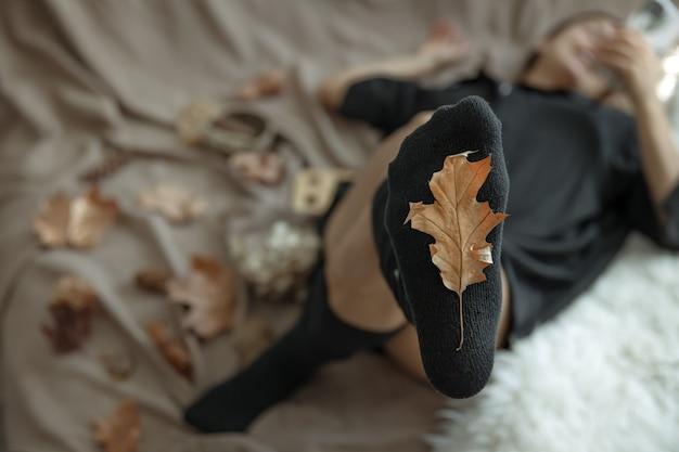 Uma mulher em meias quentes em um fundo desfocado e uma folha de outono em foco.