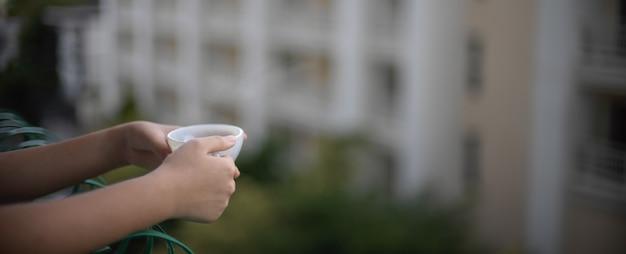 Uma mulher em pé na varanda relaxando e segurando a xícara de café da manhã