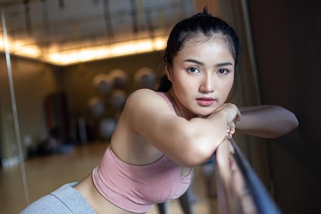 Uma mulher em pé relaxado, mãos colocadas em um trilho de aço no ginásio.
