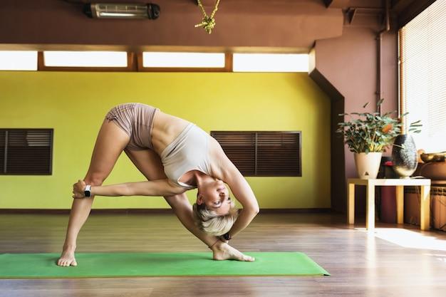 Uma mulher em roupas esportivas praticando ioga realiza o exercício trikonasana em uma pose de triângulo no estúdio