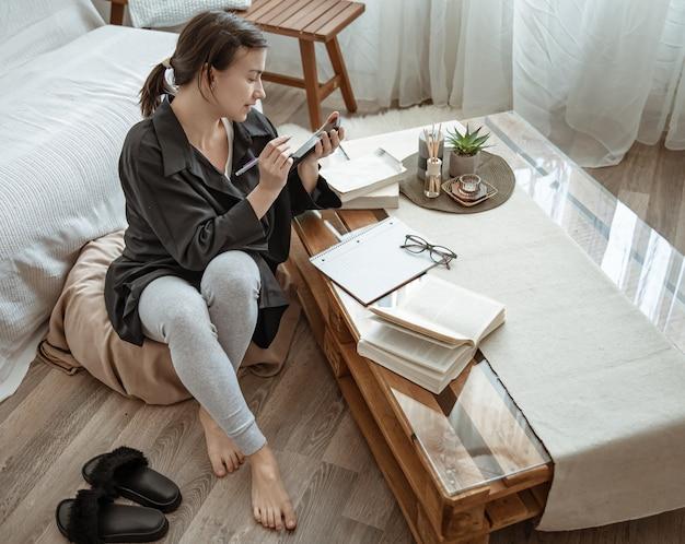 Uma mulher em sua mesa com livros e um caderno está trabalhando ou estudando remotamente.