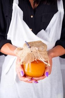Uma mulher em um avental branco detém um pote de mel