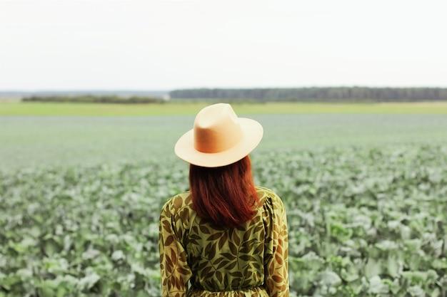 Uma mulher em um campo com repolho. estação de colheita de outono.