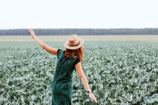 Uma mulher em um campo com repolho. estação de colheita de outono