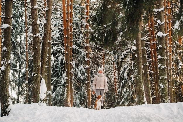 Uma mulher em um dia de inverno com seu cachorro beagle na floresta de inverno jogando.