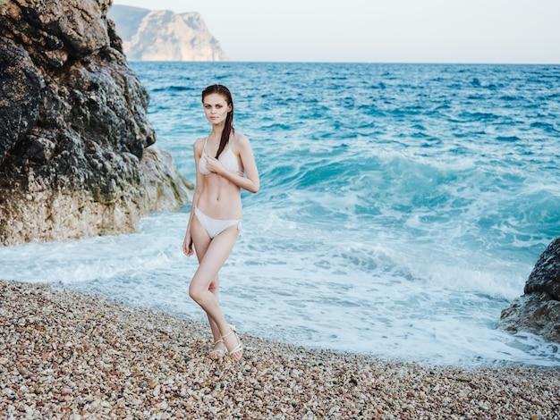 Uma mulher em um maiô branco em pleno crescimento em uma praia rochosa perto do mar, águas claras