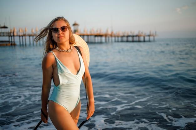 Uma mulher em um maiô e um chapéu com óculos caminha ao longo da praia ao pôr do sol. o conceito de recreação marítima. foco seletivo