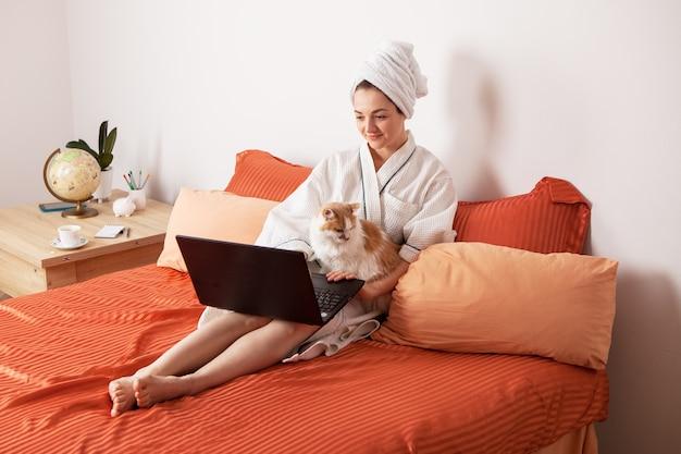 Uma mulher em um roupão de banho e uma toalha sentada na cama com um gato. educação e trabalho online em casa