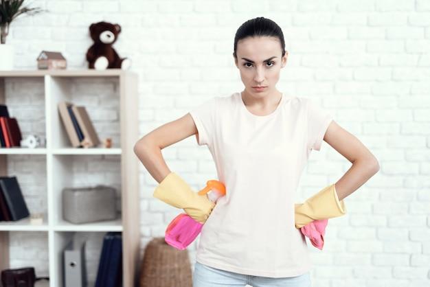 Uma mulher em um t-shirt branco em casa com fundos para a limpeza.