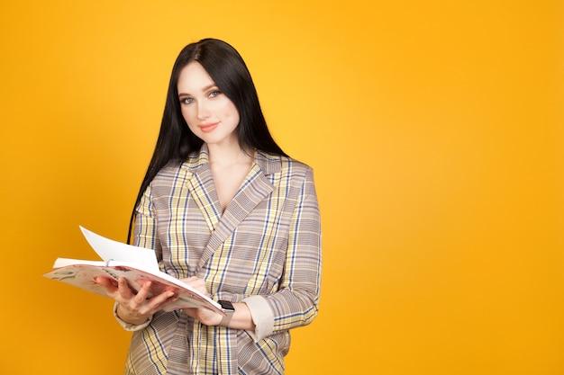 Uma mulher em um terno de negócios com um bloco de notas nas mãos, em uma parede amarela, à direita do espaço de texto, com espaço de cópia. mulher de negócios conceito, planejamento de negócios.