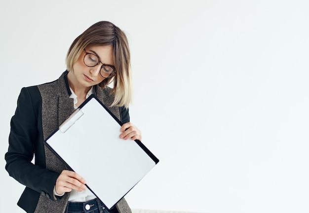 Uma mulher em um terno formal segura uma folha de papel branco nas mãos