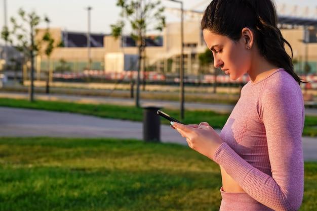 Uma mulher em um terno para yoga faz de manhã cedo com um telefone nas mãos ao amanhecer.