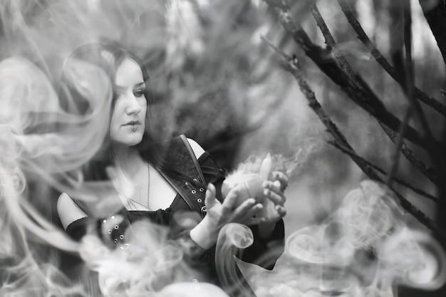 Uma mulher em um traje de bruxa em uma floresta densa em um ritual