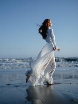 Uma mulher em um vestido branco caminha na areia molhada na costa do oceano em pleno crescimento